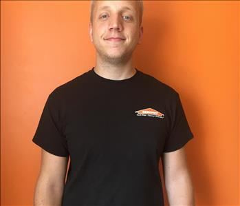Male SERVPRO employee in front of orange background.