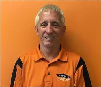 Male SERVPRO employee with blonde hair in front of orange background