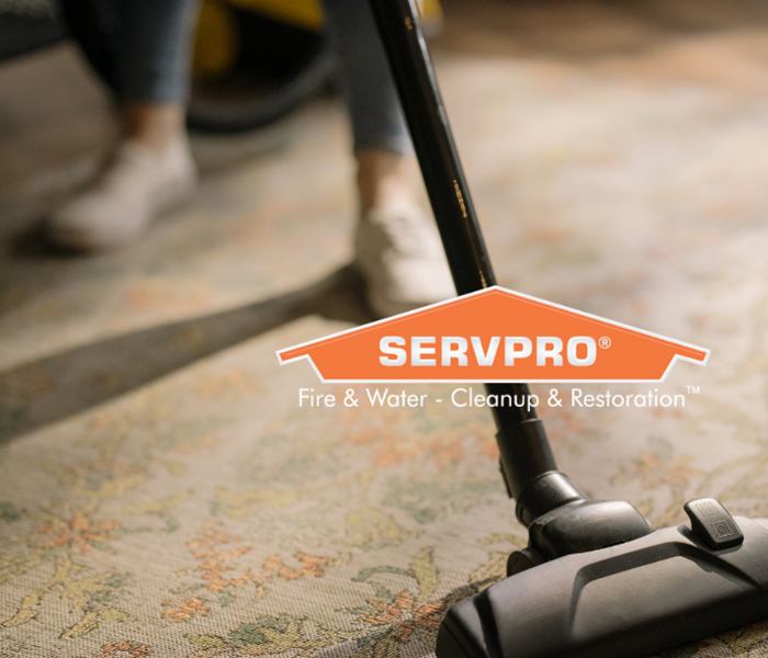 SERVPRO logo with person vacuuming in background