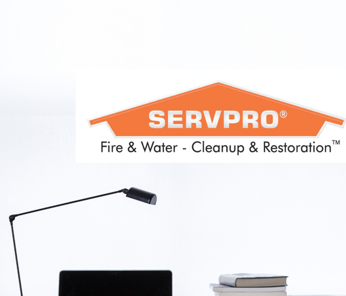 SERVPRO logo with lamp, computer and books on a desk